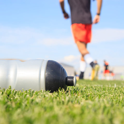 Close up of a water bottle on a grass field with people playing soccer in the background.