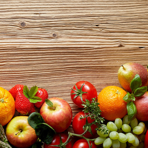 Fruits and vegetables across a wood background.