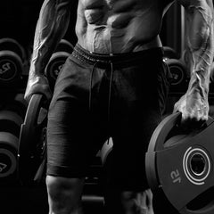 Weightlifter in a gym dressed in athletic apparel getting ready to deadlift.