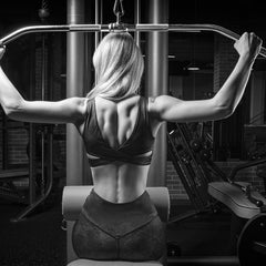 Image of a woman in athletic apparel working out her back on a fitness machine.