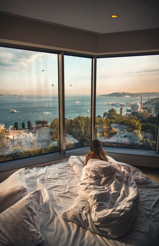 Girl in bed wrapped in a comforter looking at the view of the sea