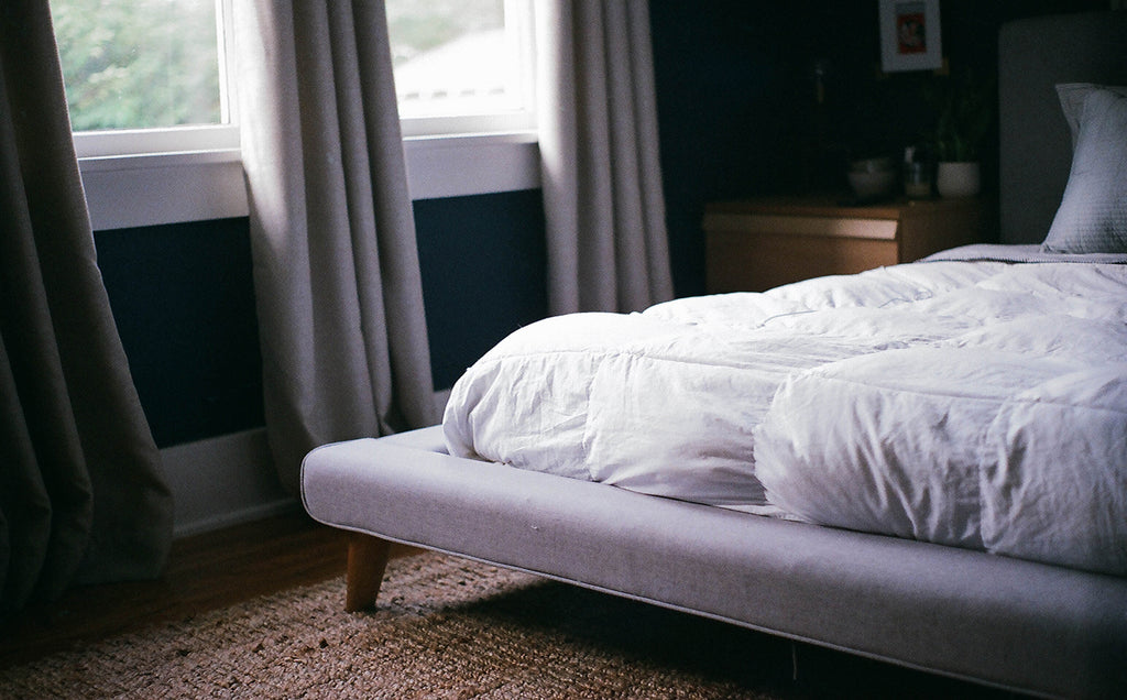 white mattress on top of a bed frame in a dark bedroom