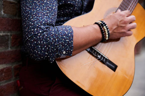 Close up on man's right arm as he plays wood guitar and shows sleeve cuffed using FLXCUF