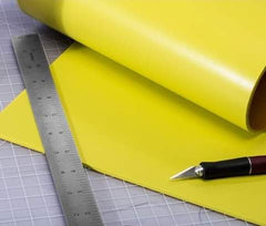 Poron XRD yellow cushion roll on a cutting board with an sharp knife and ruler