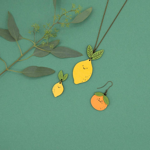 Link that sends us to the page of the collection of illustrated wooden jewelry EAT YOUR VEGGIES, by Materia Rica. In the photo there are smiling fruit jewelry, such as the Mr. Lemon necklace or the Mr. Orange or Mr. Lemon earrings.