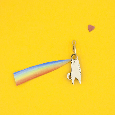 Link that sends us to the page of the FURRY BUDDIES jewelry collection, by Materia Rica. In the photo there is a HANGING CAT earring, a cream white cat hanging from a golden ring. Behind him a multi-colored trail.