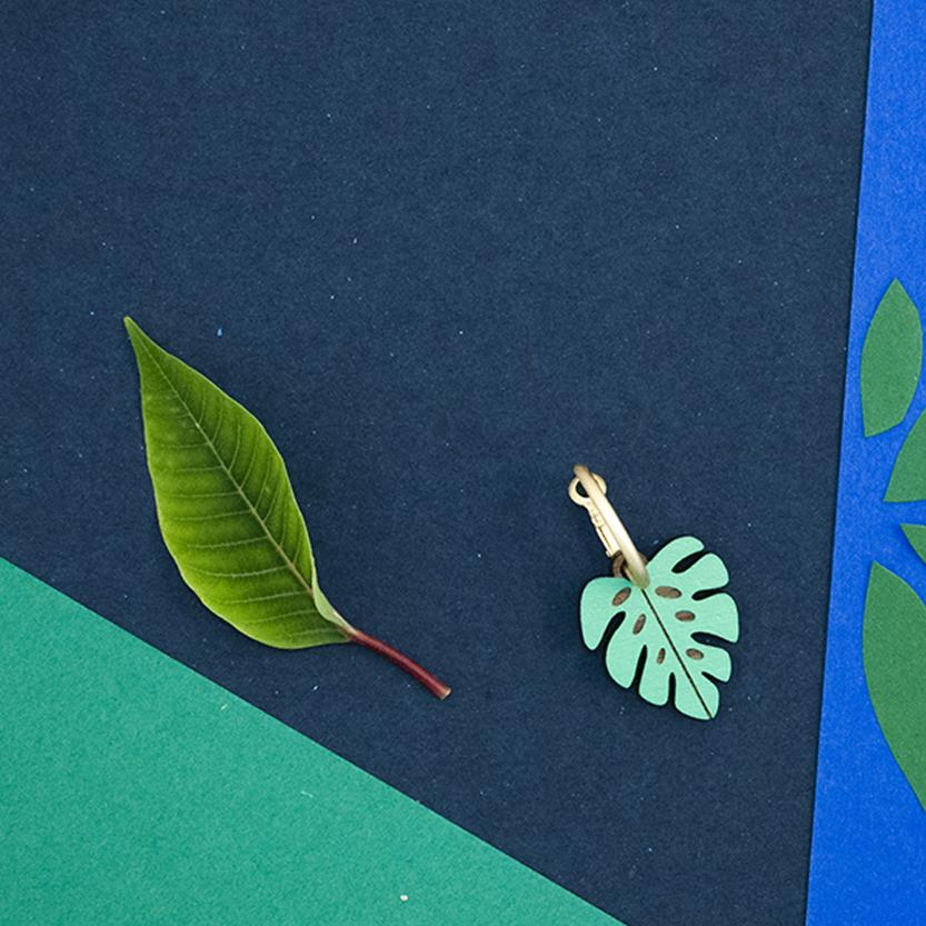Link that sends us to the page of the WOODHOOD illustrated wooden jewelry collection by Materia Rica. In the photo the MONSTERA earring, a green leaf with a golden ring.