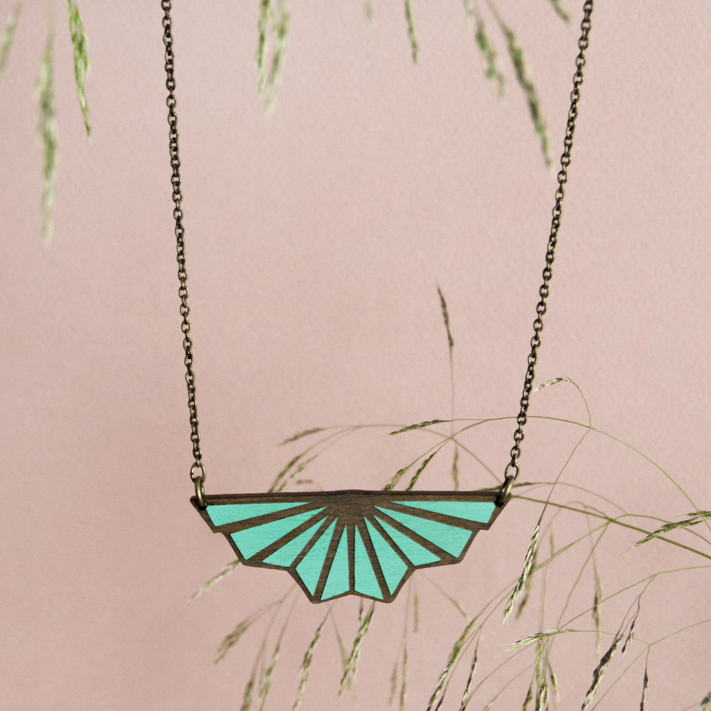 Link that sends us to the page of the collection of illustrated wooden jewelry ART DECÓ by Materia Rica. In the photo a necklace with geometric shapes in turquoise blue.