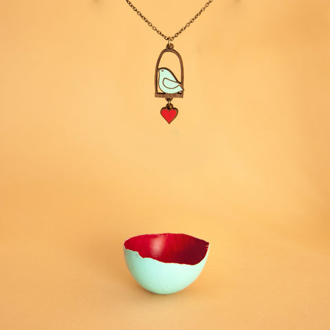 Link that sends us to the page of the LOVING DOVES illustrated wooden jewelry collection by Materia Rica. In the photo the BLUE BIRD AND LOVE necklace, a blue bird on a swing with a red heart.