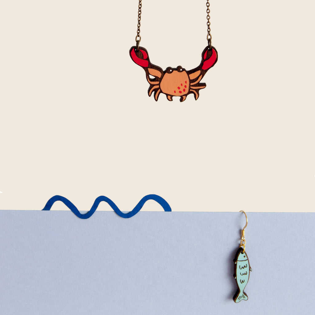 Link that sends us to the page of the SEASIDE illustrated wooden jewelry collection by Materia Rica. In the photo the MR necklace. CRAB, in red and orange tones and a blue fish earring.