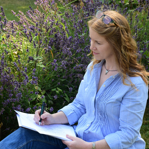Emma Lawrence drawing in the middle of a green field with lilac flowers.