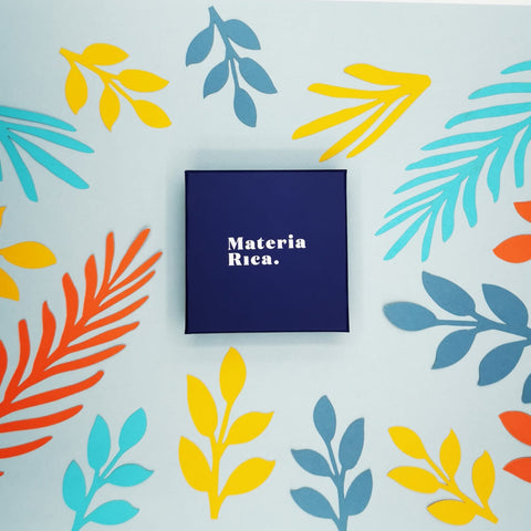 Blue case with the Materia Rica logo closed with a surprise Materia Rica jewel. The box is closed because it contains a surprise gift. The surface where the box is is full of colored cardboard silhouettes.