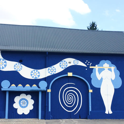 Mural painting by Lisa Junius with a woman playing a flute