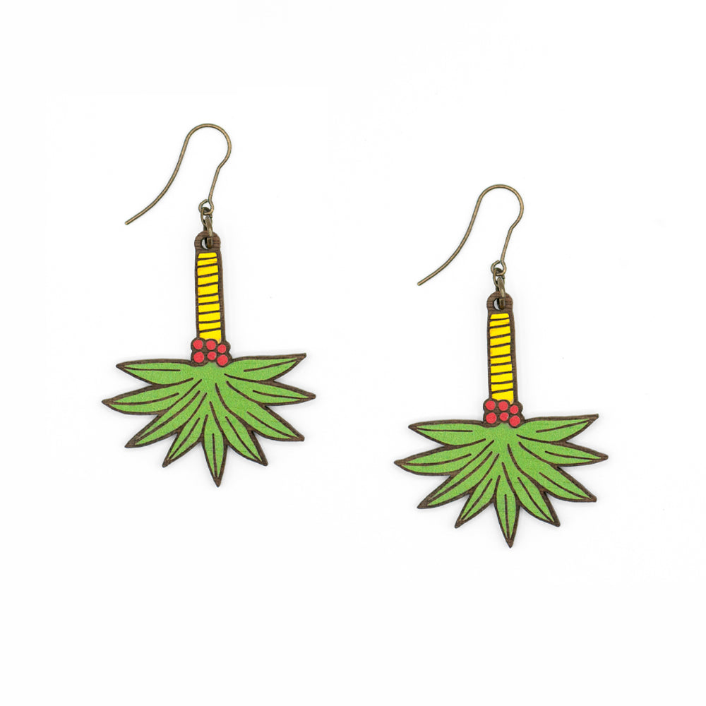 Wooden earrings in the shape of a palm tree hanging on an old gold colored hook. The earrings are painted in green and yellow and because of their shape they move when worn.