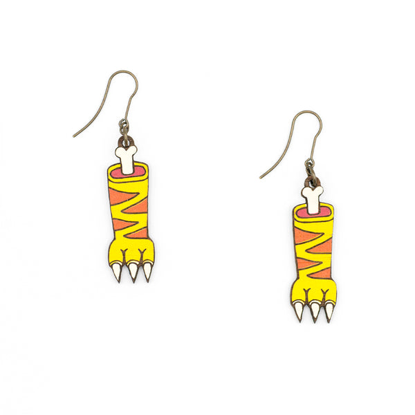Wooden earrings in the shape of a tiger's claw hanging from a hook generating a movement of the wooden piece. You can see the nails and paws of an animal and part of the bone, with lines demarcating the shapes of the skin pattern.