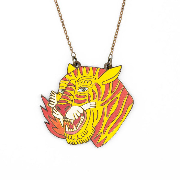 Necklace in the shape of a tiger head drawing a flame of fire from its mouth. It is an illustrated wooden gem, with engraved contours and painted in yellow and red tones.
