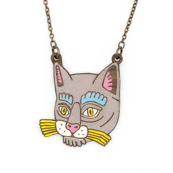 Wooden black cat face necklace with yellow mustaches and blue eyebrows. It is a piece of wood painted in black and other tones and has multiple lines, thus giving relief to the illustration.