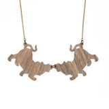 Back of the Tiger Twins necklace that reveals the two pieces of wood linked by a metal ring.