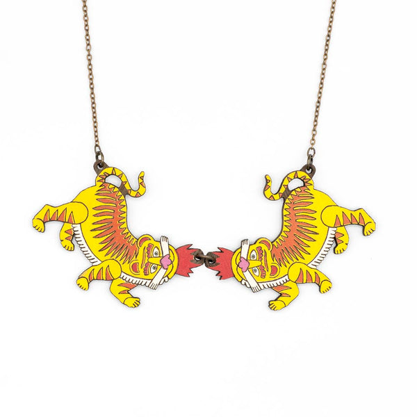 Two twin tigers necklace. They are two pieces of painted wood and joined by a metal ring. The chain is old gold and the shades of the pendant are yellow and red.