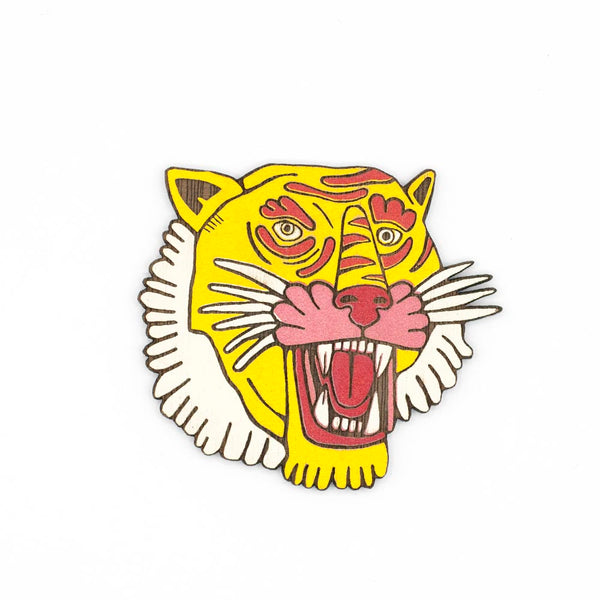 Roaring tiger face wooden brooch. The face is illustrated with engraved lines and various colors of yellow, red, pink.
