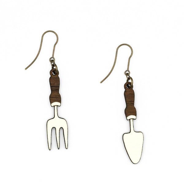 Fork Spade Earrings by Materia Rica, in the form of garden tools, in wood and white. The wooden pieces are laser cut and hand painted and closed with a metal hook in old gold.