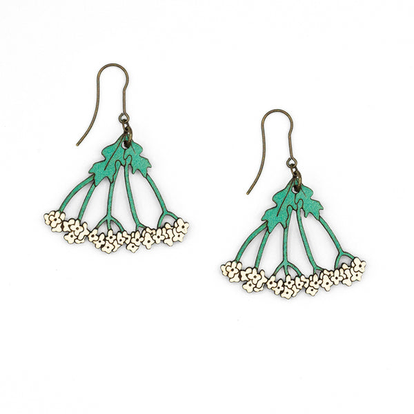 Wild Carrot earrings, shaped like wild carrot flowers, white in color and with green stems. The necklace is made of laser cut and painted wood.