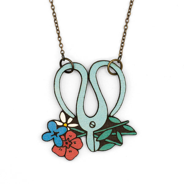 Garden Neck Scissors in the shape of blue scissors cutting colorful flowers. The necklace is made of laser cut wood.