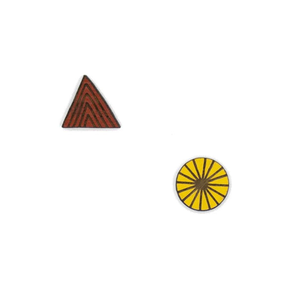 Wooden button earrings in the shape of a triangular earth red mountain and a circular yellow sun with radial stripes.
