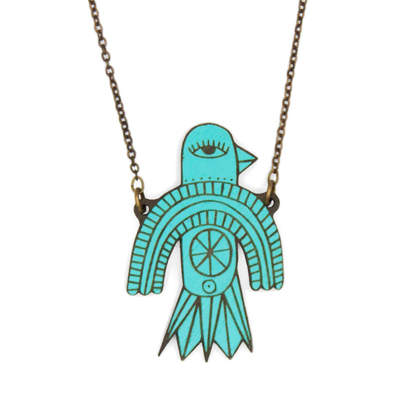 Wooden necklace in the shape of a blue bird illustrated with geometric shapes. It has an old gold chain.