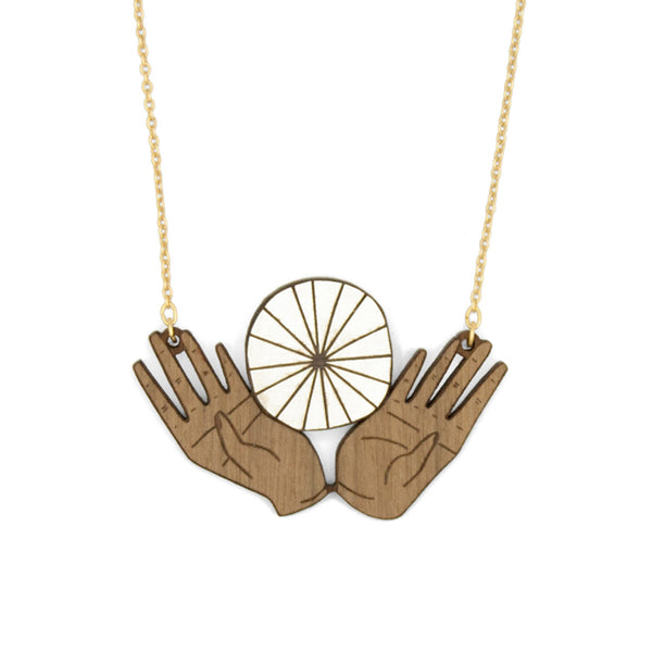 Wooden necklace with open hands and round white object in the middle held. The necklace has a matte gold chain.