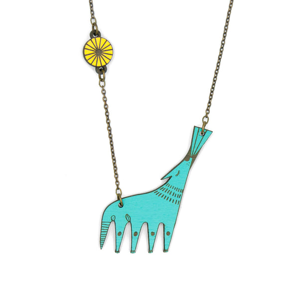 Wolf-shaped necklace howling at the moon. It is made of wood and the wolf painted in turquoise blue and the moon in yellow.