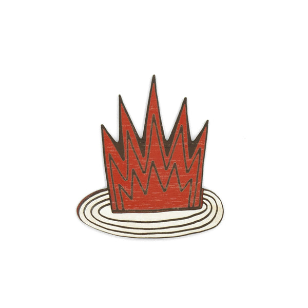 Wooden brooch painted in red tile, maroon, in the shape of fire on a white round base. It is a brooch of the brand Materia Rica.