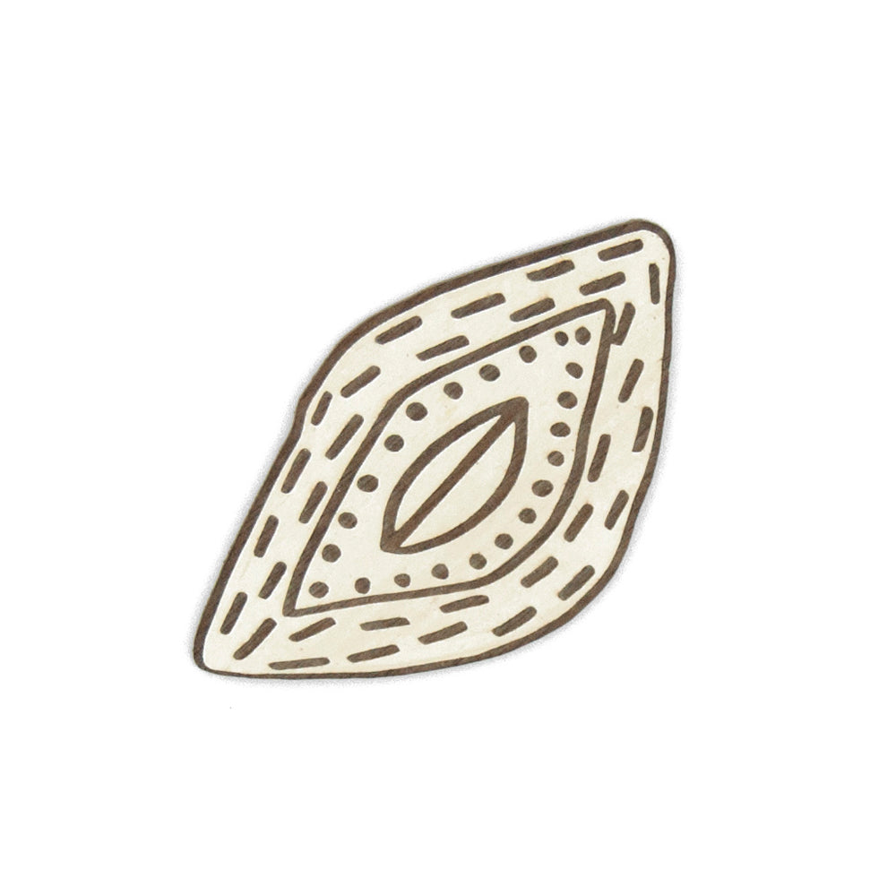 Wooden brooch in the shape of a seed painted in white.