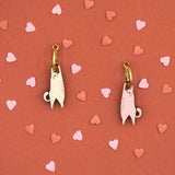 Pink and white wooden Hanging Cat earring on red background and hearts.