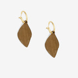 Sacred Seed earrings on the wooden back, with a matte gold ring.