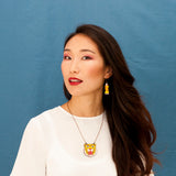 Model wearing the Walnut Leopard Necklace and Claw Earrings. They are jewels from the ROAR collection of the Materia Rica brand designed with the illustrator Asis Percales.
