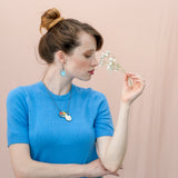 Model wearing blue wooden watering can earrings and Flowers in a Jug necklace from a jug filled with wild flowers. The jewels are made of wood and metal in shades of old gold.