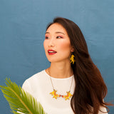 Model wearing Tiger Twins and Guardian Tiger necklace, from the ROAR collection by Materia Rica with Asis Percales. The main material is walnut wood from sustainable forests and they are painted in yellow and red tones. The best conscious gift for a lover of the feline world.