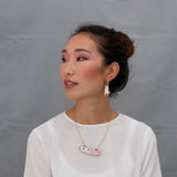 Model wearing the Hanging Cat earring, hanging from a gold hoop in her ears. He also wears the Furry Buddies necklace.