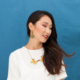 Model wearing the Tiger Twins necklace and Jungle earrings from the ROAR collection by Asis Percales and Materia Rica. The materials are sustainable and safe, making them a conscious gift for her.