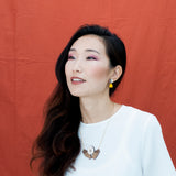 Model wearing the OFRENA necklace with hands holding a white object symbolizing an offering and Moon Light earrings.