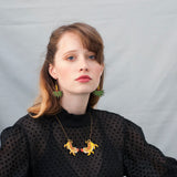 Model wearing the Tiger Twins necklace and Jungle earrings from the ROAR collection by Asis Percales and Materia Rica. The yellow and green tones stand out and the wood is FSC certified forest walnut.