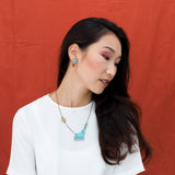 Model wearing the Howling at the Moon Wolf Necklace and Tree & Roots Earrings in Turquoise Blue and Red.
