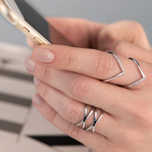 Female models hands wearing two different rings, typing on a smartphone.