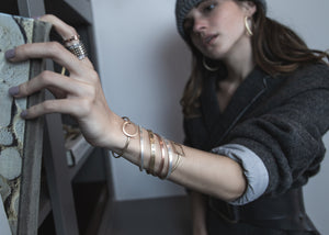 Young woman taking a book off of a book shelf, with two rings, and multiple thin bangle bracelets being the focus of the picture.