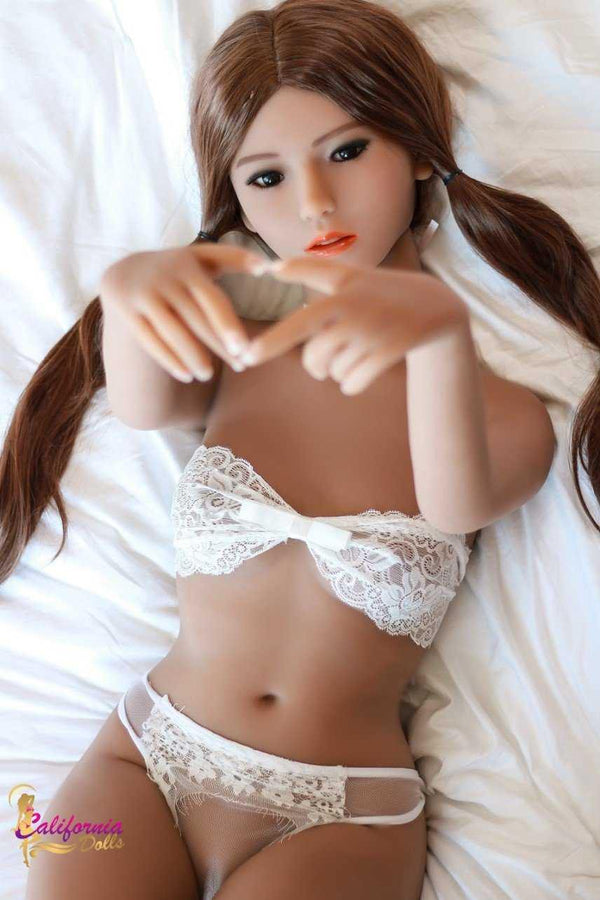 Sex doll making a little heart shape with her fingers.