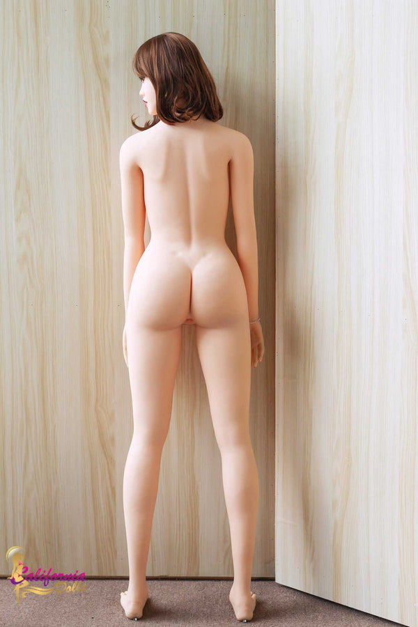 Totally nude sex doll stands facing wall.