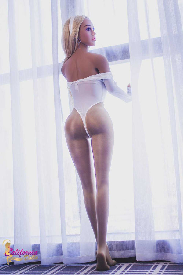 Slender curvy sex doll with long legs stands.