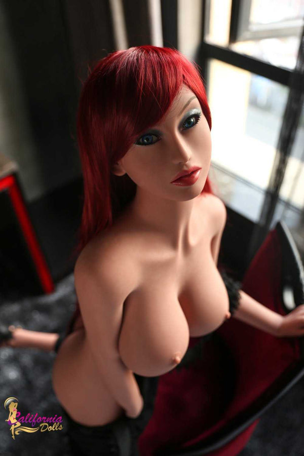 Nude redhead sex doll with large perky breast.