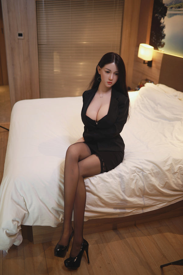 Super premium sex doll sitting on bed.